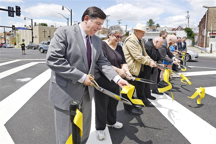 Brookline Boulevard Yellow ribbon flies as Pittsburgh Mayor Bill Peduto, left, and a host of dignitaries cut the ceremonial ribbon marking the end of the 17 month, $5.35 million reconstruction of Brookline Boulevard.