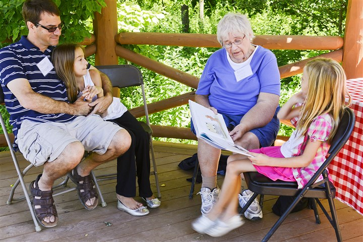 20140725rldPittsburghBotanic02_West-1 Beth McGill Ellis, center, of Barto, reads to her granddaughters Kara Frazier, 10, left, and Ashlyn Frazier, 7, at the Pittsburgh Botanic Garden in North Fayette. The McGill's chicken farm was sold to Allegheny County and has become part of the 460-acre Pittsburgh Botanic Garden, which will open Friday. The McGill family is holding a reunion at the garden.