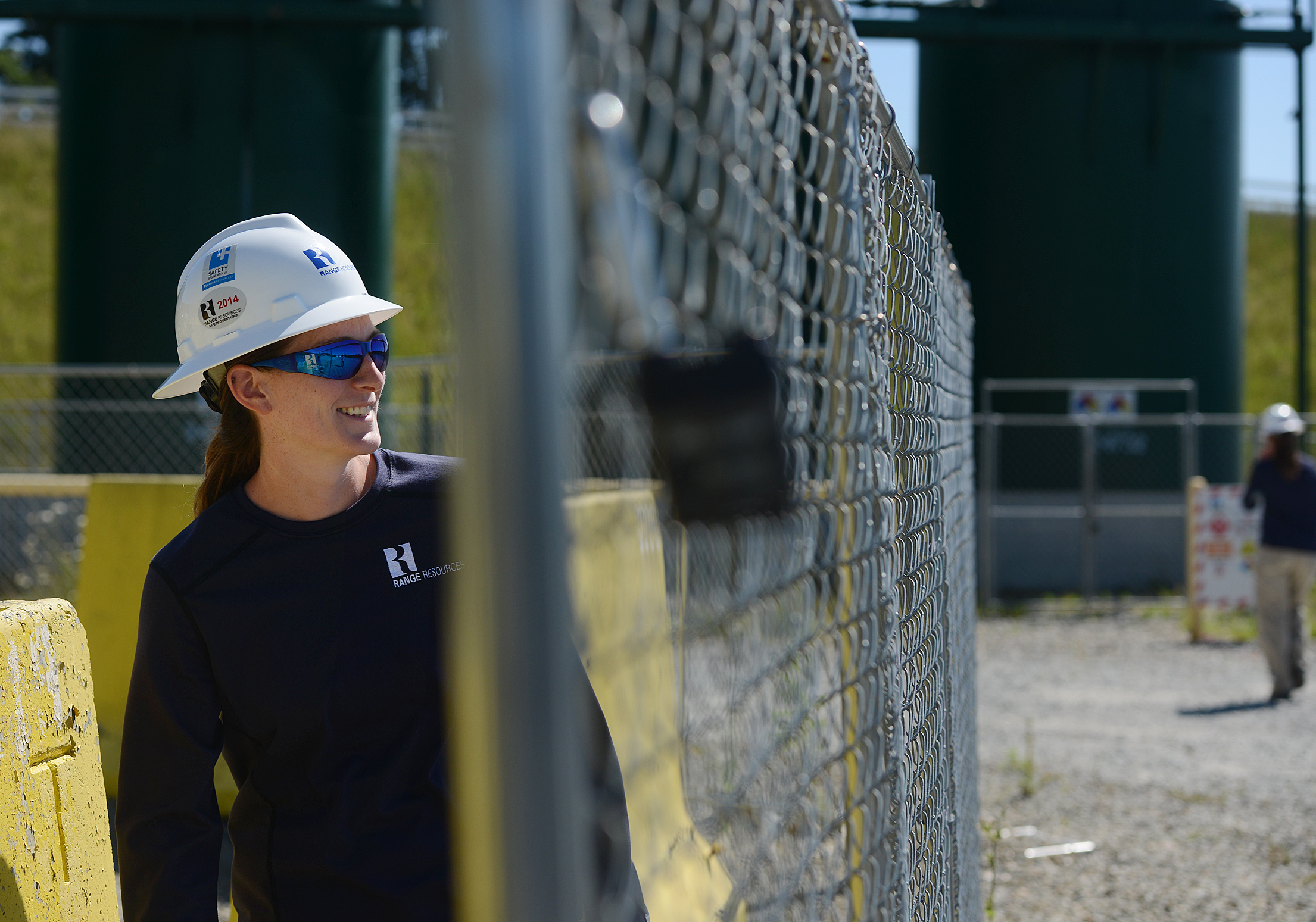 20140725jrWomenBiz3-2 Hanna McAvoy, 28, of Burgettstown, an environmental technician with Range Resources, checks the Hoskins well pad on Old Hickory Ridge Road in July.