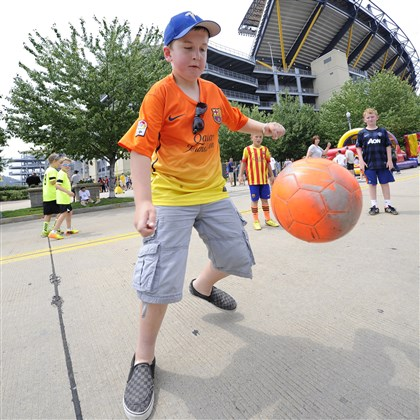 20140727CMGuinnessCupSports004 Holden Green, 11, of Chicago plays soccer with friends outside of Heinz Field before the Guinness International Champions Cup between AC Milan and Manchester City.