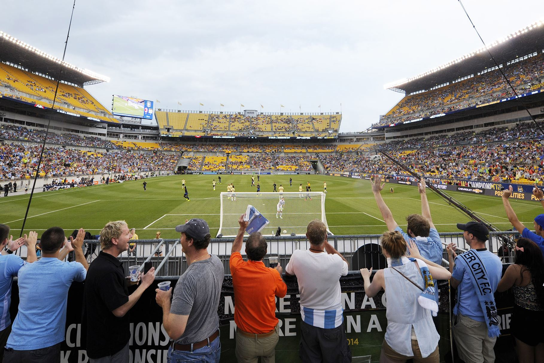Fans cheer a goal by Manchester City in the Guinness International Champions Cup match Sunday between AC Milan and Manchester City at Heinz Field.