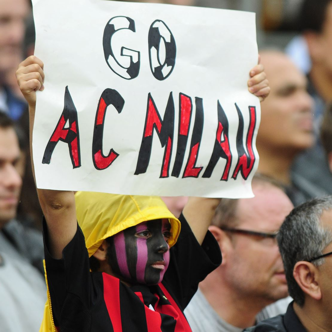A young AC Milan fan cheers on his team with face paint and a sign Sunday at Heinz Field.