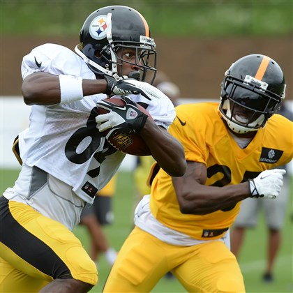 20140728pdSteelersSports10-3 Antonio Brown makes catch and picks up yardage during afternoon workouts in the rain Monday at Saint Vincent College.