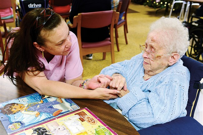 Caregiver Denise Schilling talks with Gloria Biddle, 97, during the adult day care program at the Elizabeth Seton Center in Brookline.