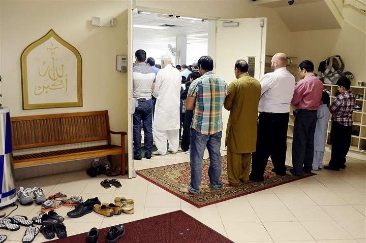 20140728dsRamadanLocal04-3 Because of crowding, men had to stand in the doorway during prayer services for Eid al-Fitr services at the Muslim Community Center of Greater Pittsburgh in Monroeville.