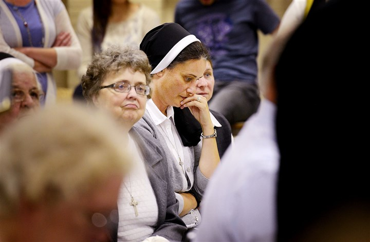 Holy Family Institute Emsworth hearing Sister Daniela Bronka, center, listens during a public meeting Tuesday night regarding the Holy Family Institute's plans to temporarily house dozens of Central American children in Emsworth.