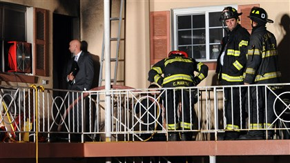 20140730JHLocalFire02-1 Pleasant Hills firemen stand outside a second story apartment at the Neopolitan Suites apartment complex on Curry Hollow Road.