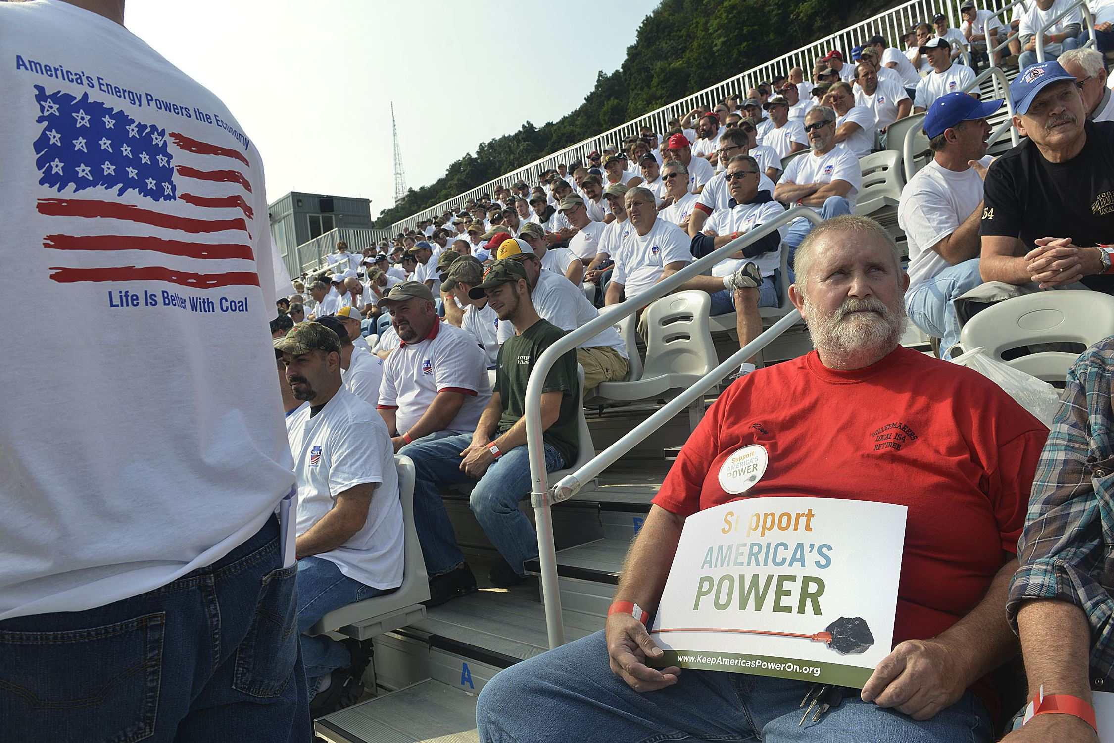 20140730lrcoallocal08-6 Ray Chester, right, a retired boilermaker from Local 154, joins hundreds of people in the stands at Highmark Stadium for a rally in support of American energy and jobs in the coal industry today.