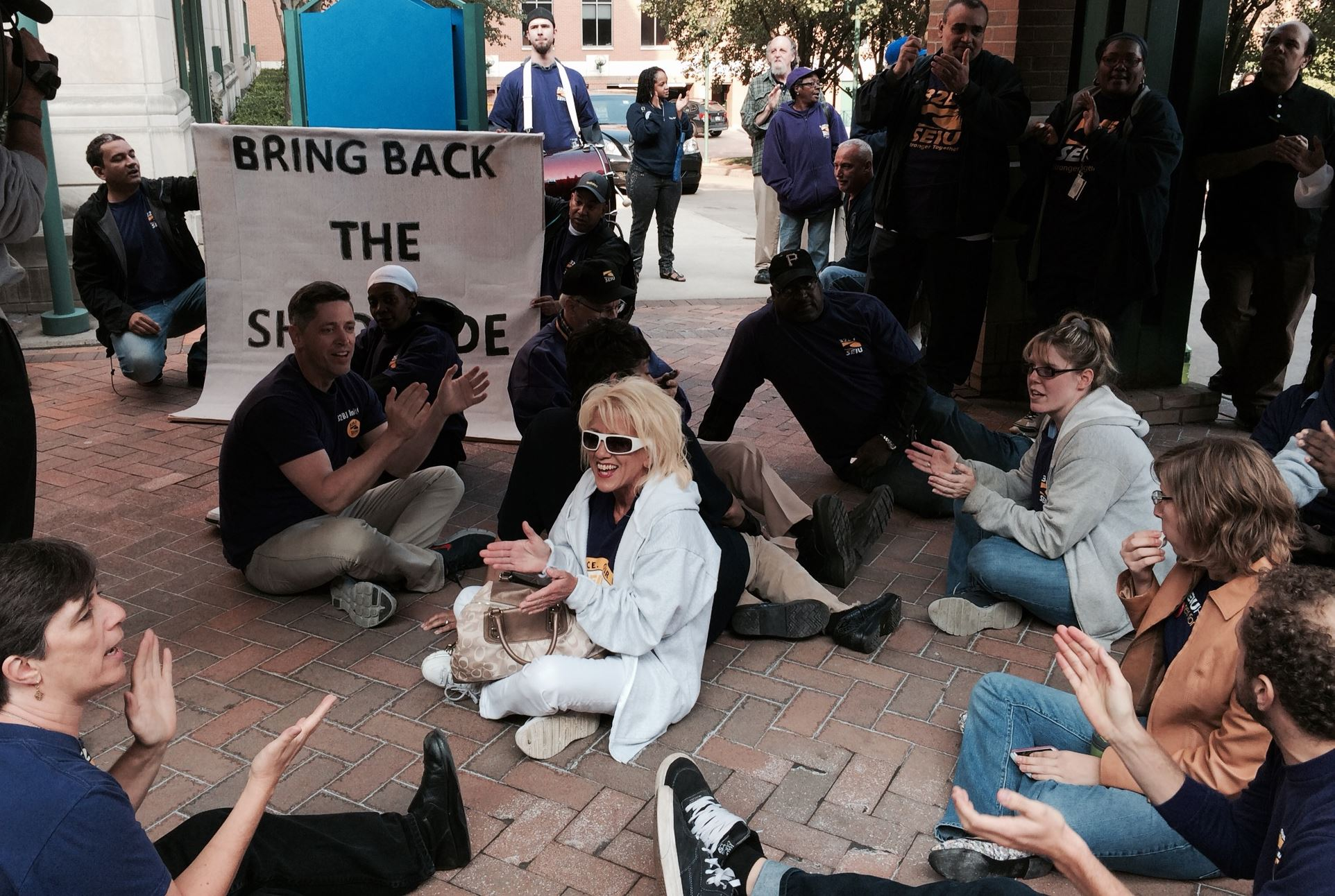 Protesters stage a sit-in near the entrance to UPMC Shadyside Hospital Wednesday. Six people were cited during the sit-in, which was protesting the replacement of a cleaning contract with a non-union staff.