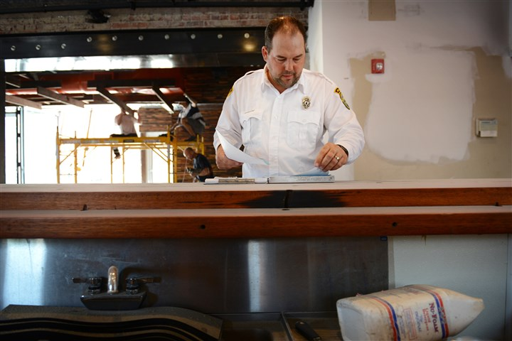 Pittsburgh Bureau of Building Inspection Brian Ralson, a Pittsburgh Bureau of Building Inspection employee, goes over his inspection paperwork on a new restaurant Thursday in the South Side.