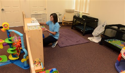 20140730RARseennursery5-4 Kayla Olson sorts toys in the infant area at Jeremiah's Place in East Liberty.