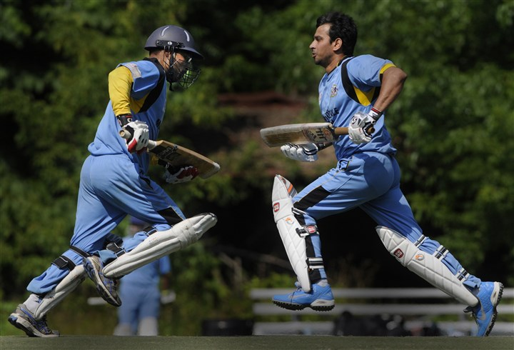 20140712ppCricket4SUNMAG Monroeville United Cricket Club's Santhosh Prasad, left, and Ravi Patel cross the pitch scoring during a game against the Classics at Edgebrook Field in South Park.