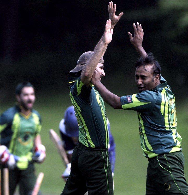 20140802ppcricket3SUNMAG-5 Ohio Challengers bowler Shafi Mohammed celebrates with teammate Aniq Ahmed during a game against PittsPunters at Edgebrook Field in South Park.