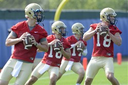 Pitt quarterbacks (from left) Adam Bertke (7), Chad Vojtik (16), Trey Anderson (11), and Joe Repischak (18) during passing drills on the first day of preseason football practice earlier this month at their training facility on the South Side.