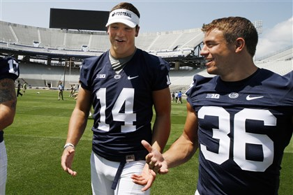 psu0805 Penn State quarterback Christian Hackenberg (14) and running back Deron Thompson walk off the field Monday at Beaver Stadium after participating in the team's media day in University Park, Pa.