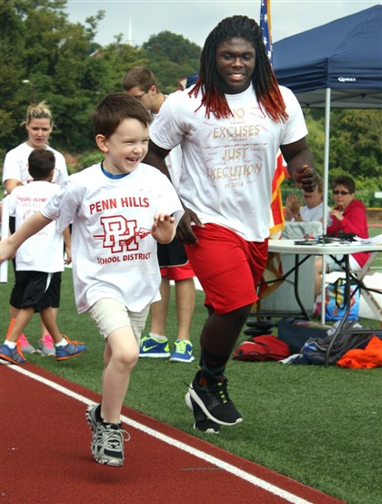 specialOly2 Kindergartner Ryan Reynolds runs in the 100-yard relay with assistance from 11th-grader Tyler Glanton.