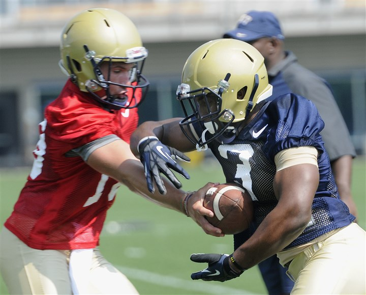 20140804radPittPracticeSpts04-3 Running back Nicholas Grigsby takes a handoff from quarterback Chad Voytik on the first day of Pitt's preseason football practice Monday at their training facility on the South Side. Writer: Werner. Story Slug: unknown
