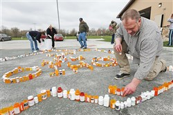 Kyle Schalow, right, and others, build a Rx Epidermic Memorial out of empty prescription drug bottles in Homecoming Park in Springfield Township, Ohio.