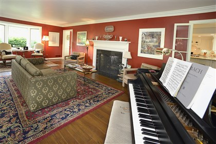 The living room. The living room is painted cherry red and features one of two wood-burning fireplaces.