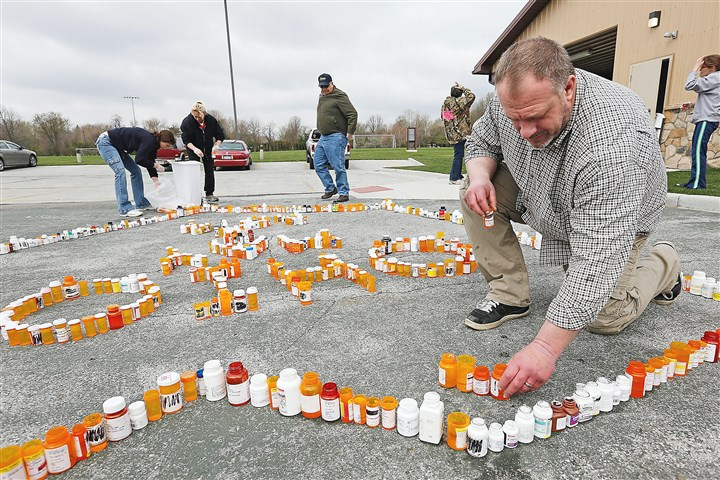 pain Kyle Schalow, right, and others, build a Rx Epidermic Memorial out of empty prescription drug bottles in Homecoming Park in Springfield Township, Ohio.
