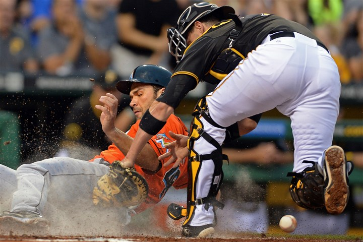 20140805mfbucssports06 The Marlins' Garrett Jones scores against Pirates' Chris Stewart in the fourth inning at PNC Park Tuesday night.