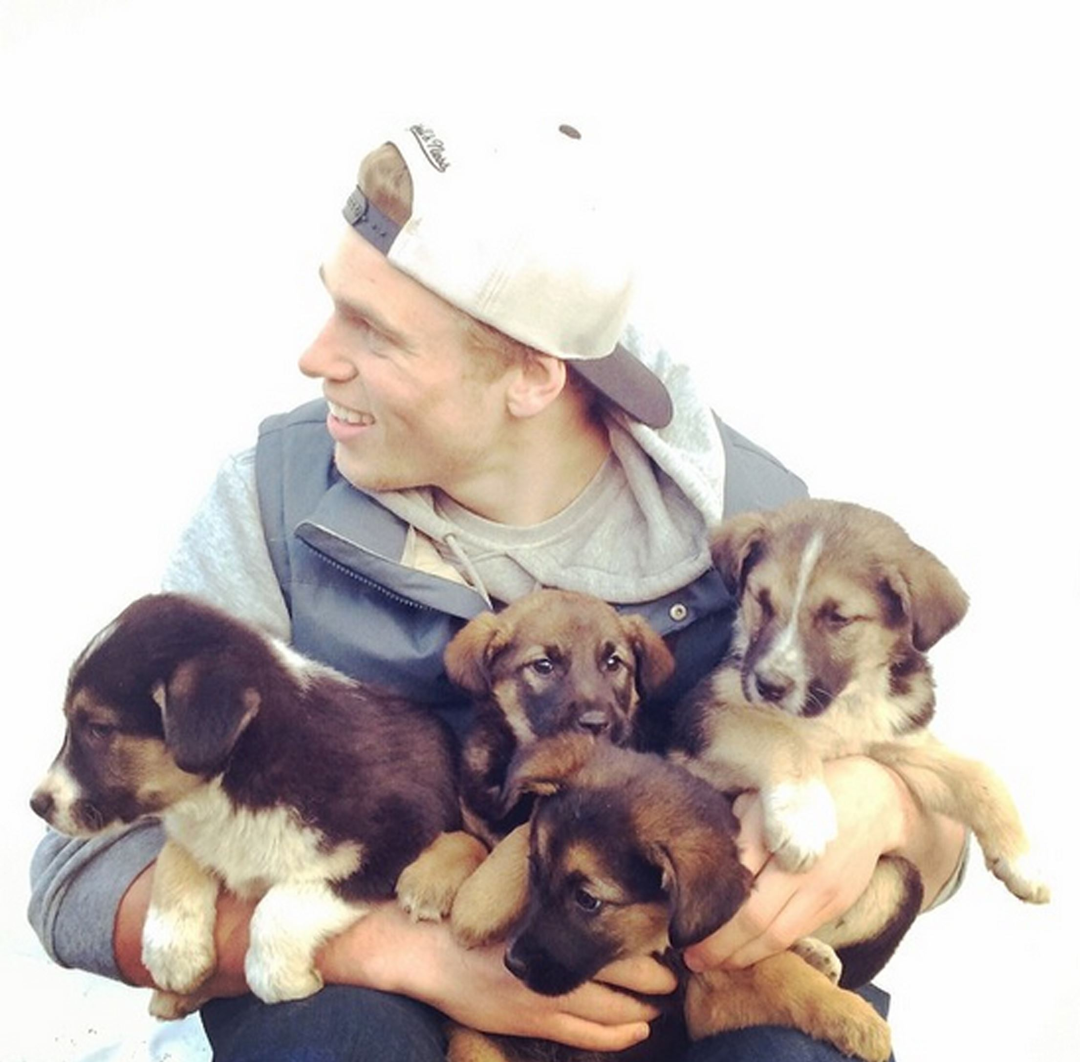 20140806hopettales0809AAmag Gus Kenworthy in the Olympic Village in Sochi, Russia, with the street puppies he found and rescued. This picture, taken by his friend, freelance photographer Robin Macdonald, went viral on social media and deluged the silver medalist with interview requests from the media.