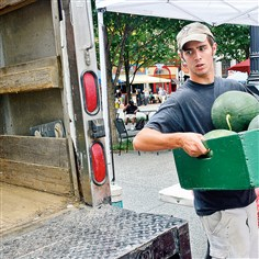 20140807lrmarketclosestandalone04-3 Scott Glovier hoists a box of watermelons into the back of the farm's truck as he helps close down the Simmons Farm stand Thursday at the farmers market in Market Square.