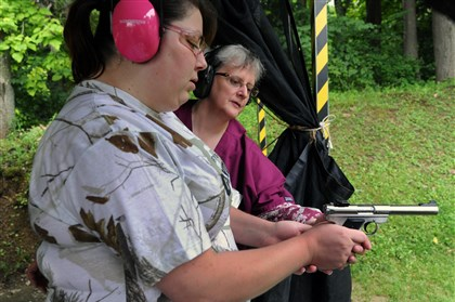 Joyce Lichtenfels and Ashley Lake Joyce Lichtenfels, back, a certified instructor from the Irwin Sportsmen Association, shows Ashley Lake, front, how to handle a gun before target shooting.