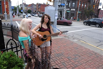 20140810ssPedSafety5-5 Mckenzin Sprague, 16, left, and Darah Appling, 18, both of Erie, sing outside of the farmers market at 18th and East Carson streets.