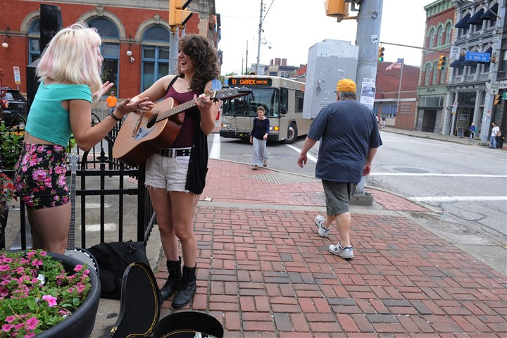 20140810ssPedSafety3-3 Mckenzin Sprague, 16, left, and Darah Appling, 18, both of Erie, sing outside of the farmer's market at 18th and East Carson Streets.
