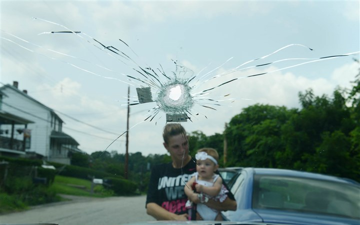20140807MWHshootingLocal04-3 Amy Calabrese, seen holding her daughter Kendall Desabatino, behind a bullet hole, gives interviews on Thursday, Aug. next to the SUV where Baldwin police shot her boyfriend.