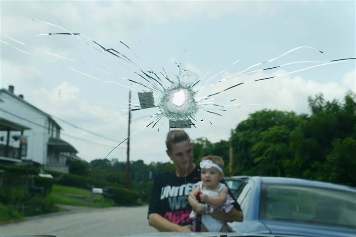 20140807MWHshootingLocal04-3 Amy Calabrese, seen holding her daughter Kendall DeSabetino, 7 months, behind a bullet hole.