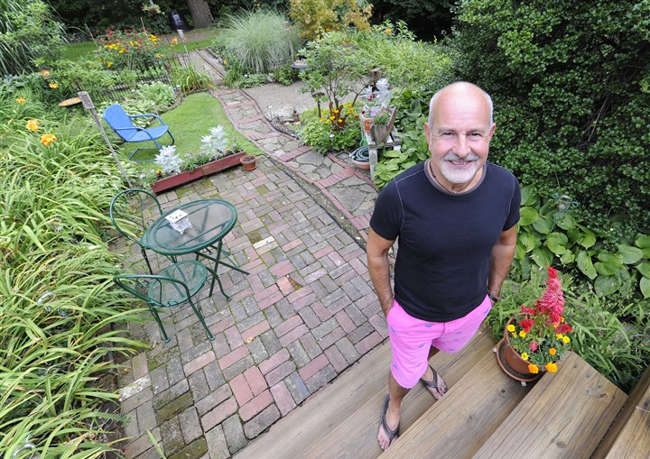 20140807CMGardenMag001 Eric D'Ambrogi on the steps leading into his backyard. His garden won the small garden category of the Great Gardens Contest.