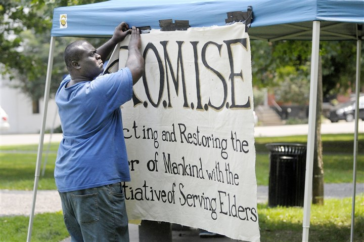 20140809ttLostLocal99 Brian Brassell of the North Side hangs a banner for the P.R.O.M.I.S.E. organization at the Annual Jehru Donaldson Gathering of Lost Loved Ones in Allegheny Commons Park on Saturday.