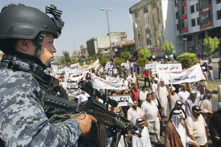 iraqS An Iraqi police officer stands guard during a demonstration in support of Iraqi Prime Minister Nouri al-Maliki on Saturday in Baghdad.