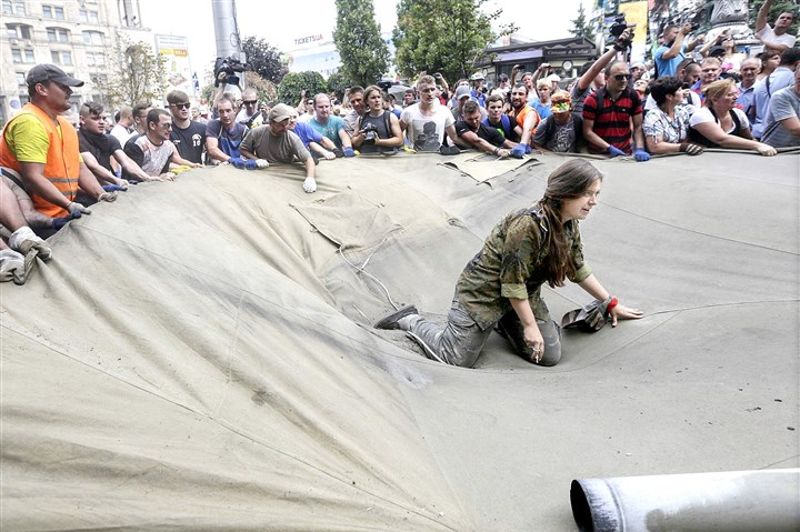 ukraine49S A protester tries to prevent municipal workers and volunteers from clearing away tents Saturday at Independence Square in Kiev, Ukraine.