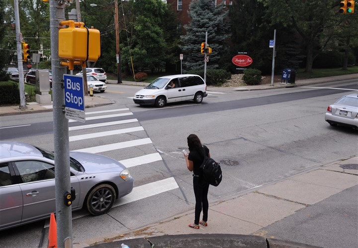 20140809ssPedestrian2  A pedestrian waits to cross the intersection of Fifth Avenue and South Aiken Street in Shadyside.