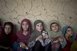 Afghan refugee girls listen to their teacher during their daily madrassa, or Islamic school, lessons at a mosque on the outskirts of Islamabad, Pakistan, on Aug. 11, 2014.