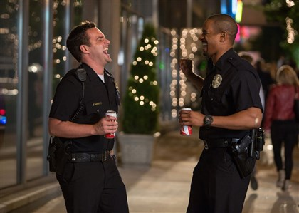 "letsbecops0813 Ryan, left, played by Jake Johnson, and Justin, portrayed by Damon Wayans Jr., think pretending to be police officers is a laughing matter but that will change in ""Let's Be Cops."""