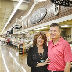 20140811dsGrocersBiz02-1 Owners Debbie and Tom Jamieson pose together in the Shop 'n Save at 150 Walnut Hill Road near Uniontown.
