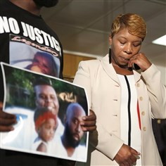 brownMom Lesley McSpadden, the mother of 18-year-old Michael Brown, with Brown's father, Michael Brown Sr., holding up a family picture of himself, his son, and a young child during a news conference Aug. 11.