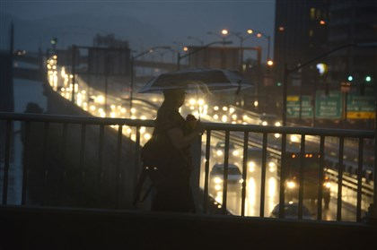 20140812dsRainLocal.jpg A pedestrian crosses the Smithfield Street Bridge over traffic on the Parkway East during a downpour this morning.