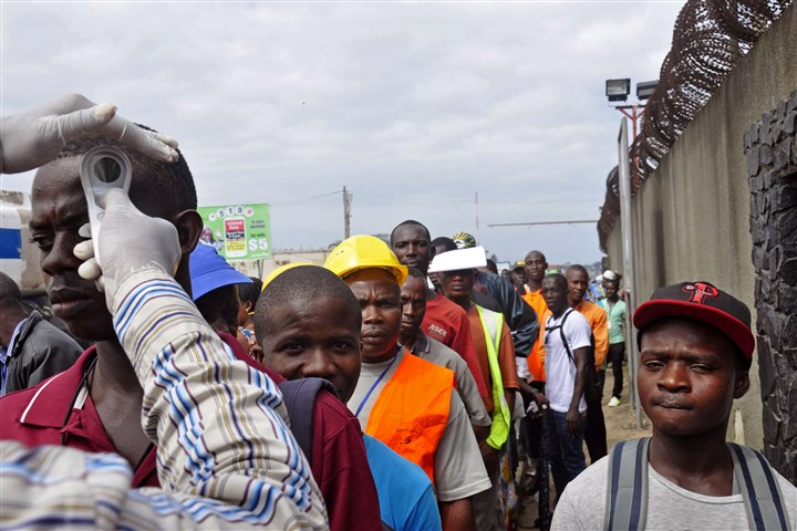 West Africa Ebola 0812 Workers have their temperature taken Monday before entering the Freeport area, an important commercial port facility, in Monrovia, Liberia.