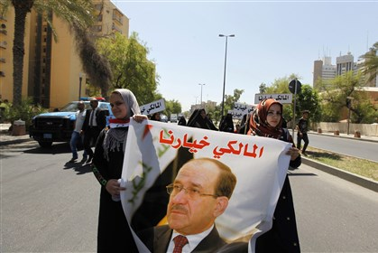 IRAQ-MALIKI 0813 Iraqis carry portraits of incumbent Iraqi Prime Minister Nuri al-Maliki as they gather in support of him in Baghdad today.