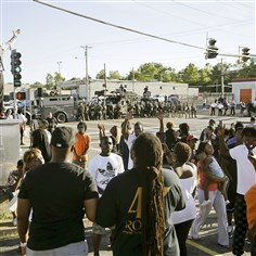 9rw00nb0 A man tries to calm a group of protesters Wednesday as police stand in the distance in Ferguson, Mo. Tensions have been high in the St. Louis suburb since Saturday, when a white police officer fatally shot Michael Brown, an unarmed black teenager.