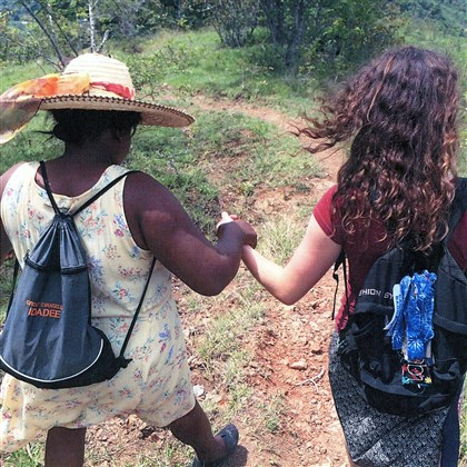 Missionary Haitian Missionary Mouslyne Michel and North Allegheny senior Tabitha White walking down the mountain from Port Saint Francis.