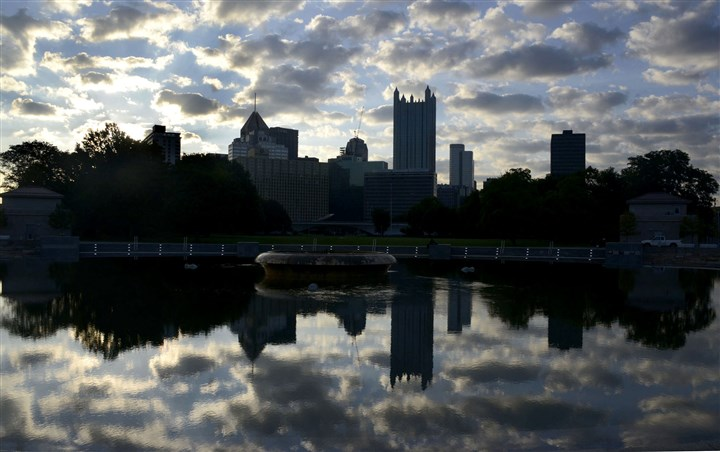 20140815dsReflectingCloudsLocal01 Early morning clouds of the Pittsburgh skyline are reflective in a quiet Fountain pool at Point State Park on Friday.