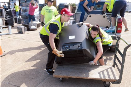 "20140816ttRecycleLocal (1) Volunteers Ryan Reilly of Oakmont, left, and Nikia Steele of Brackenridge lift a TV from a vehicle onto a cart at a ""Hard to Recycle"" collection sponsored by the Pennsylvania Resources Council and partners at the Allegheny County Airport in West Mifflin."