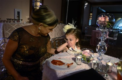 20140816bwSarrisSeen34-13 Beverly Rionda helps her grandaughter Adelena Hadad with some rice during the pre-dinner reception at the Westin Convention Center.
