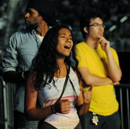20140816DARThreeRivers9 Malkyah Biley, 14, of Aliquippa, sings along during a performance by Christian rock performer Lacey on Saturday at the Consol Energy Center. Her father, Herb, stands in the background.